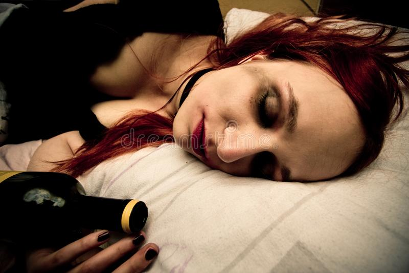 Mujer joven que miente en cama con la botella de vino fotografía de archivo libre de regalías