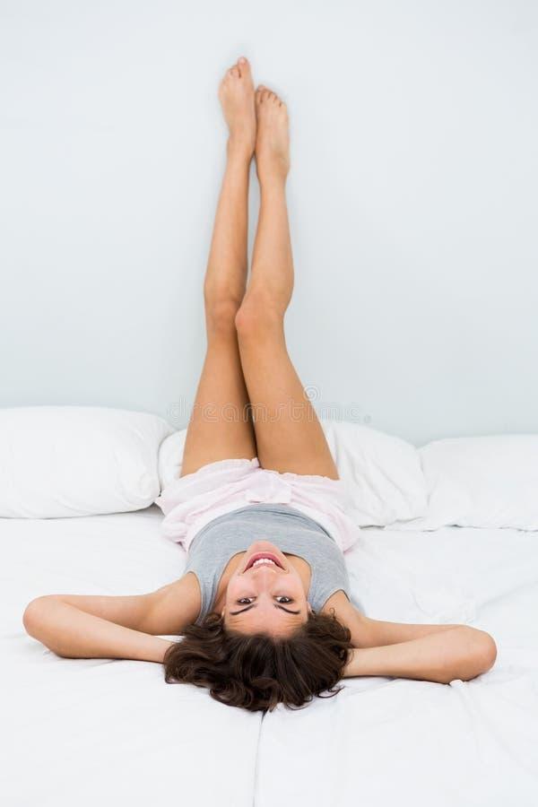 Mujer joven que miente en cama con sus pies para arriba foto de archivo libre de regalías