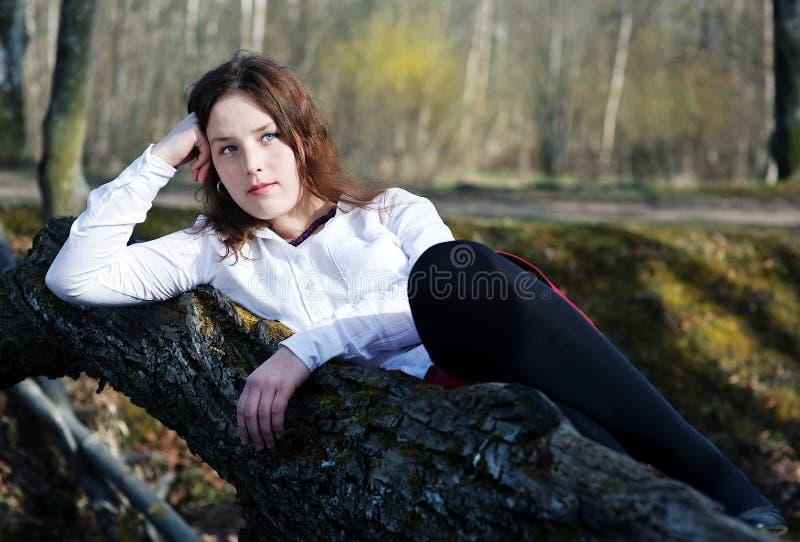 Mujer joven que miente en el árbol fotos de archivo libres de regalías