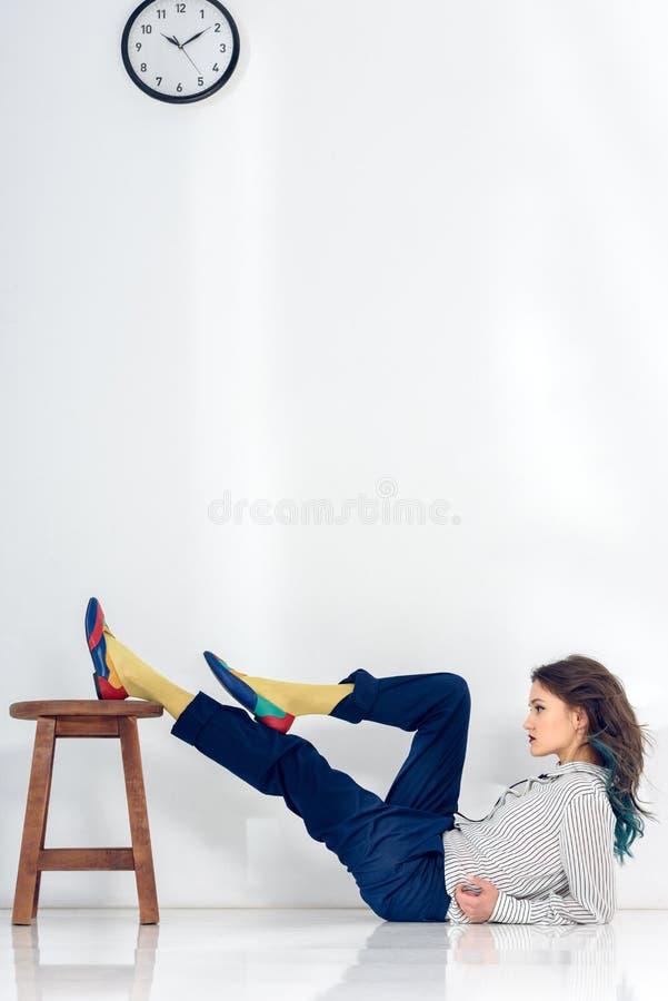 Mujer joven que miente en el piso blanco imagen de archivo libre de regalías