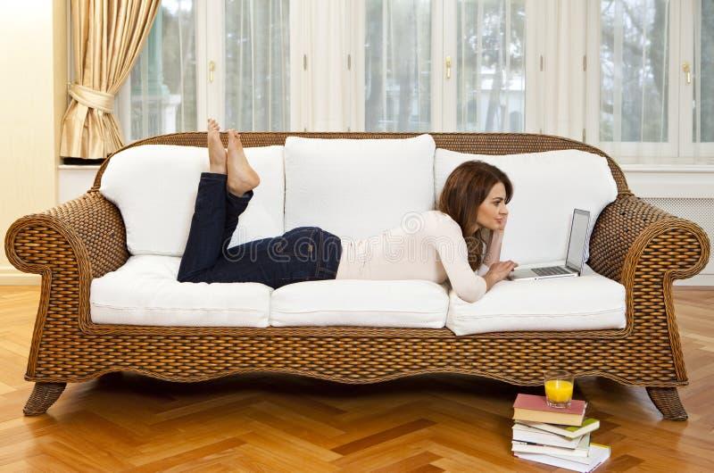 Mujer joven que miente en el sofá con el ordenador portátil fotos de archivo libres de regalías