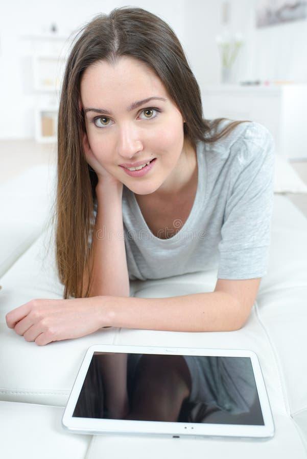 Mujer joven que miente en el sofá con PC de la tableta en casa fotos de archivo