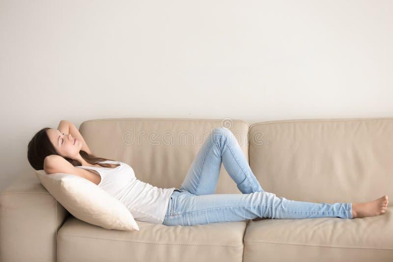Mujer joven que miente en el sofá, relajándose con las manos detrás de la cabeza fotos de archivo