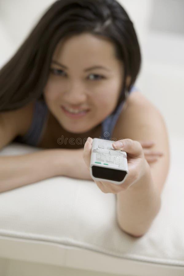 Mujer joven que miente en el sofá usando foco personal teledirigido de la perspectiva en teledirigido foto de archivo