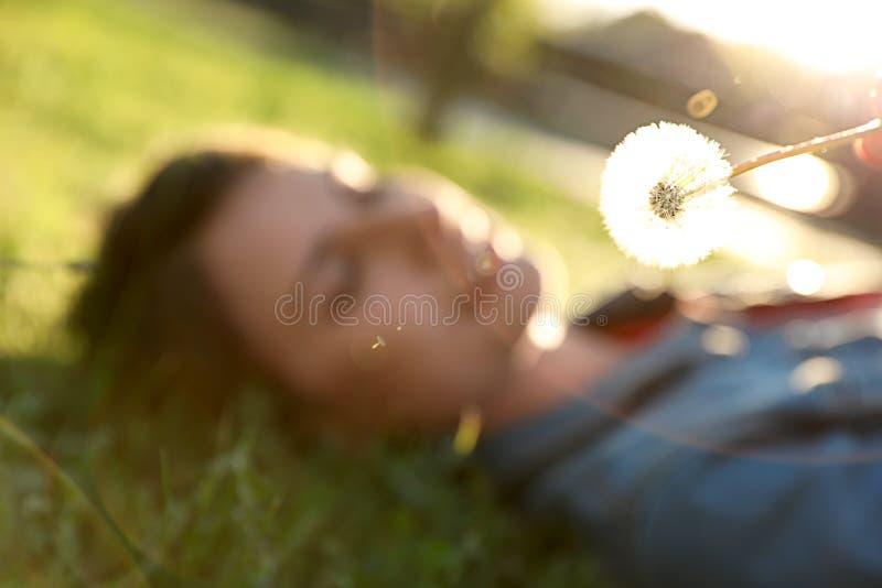 Mujer joven que miente en hierba verde en el parque, foco en el diente de león La alergia libera imagen de archivo libre de regalías