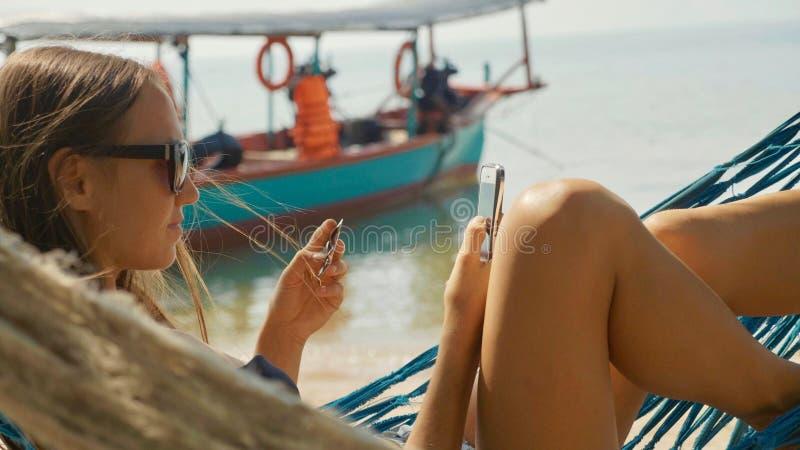 Mujer joven que miente en la hamaca con la tarjeta elegante del teléfono y de banco en la playa arenosa foto de archivo