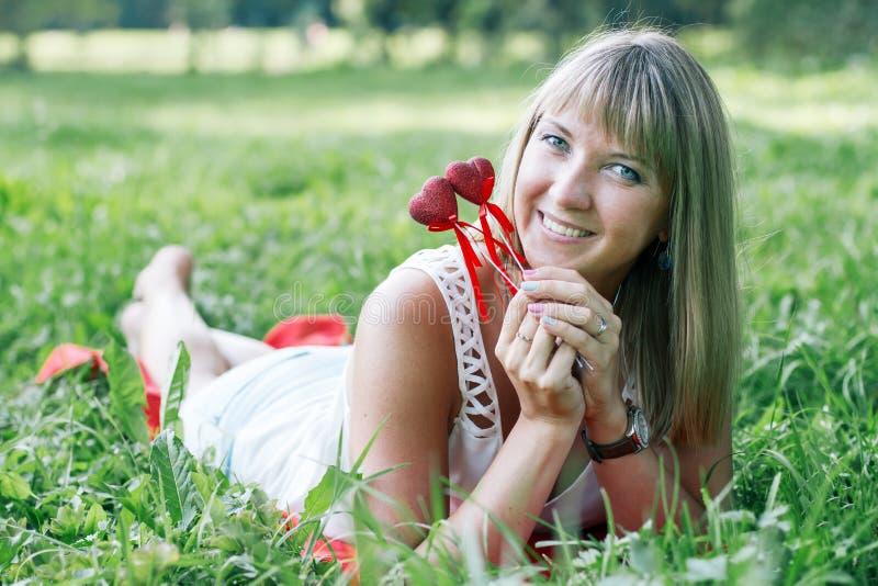 Mujer joven que miente en la hierba en el parque fotografía de archivo