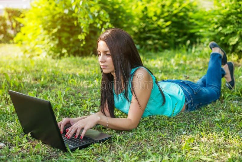 Mujer joven que miente en la hierba, usando el ordenador portátil y mecanografiar imagen de archivo libre de regalías