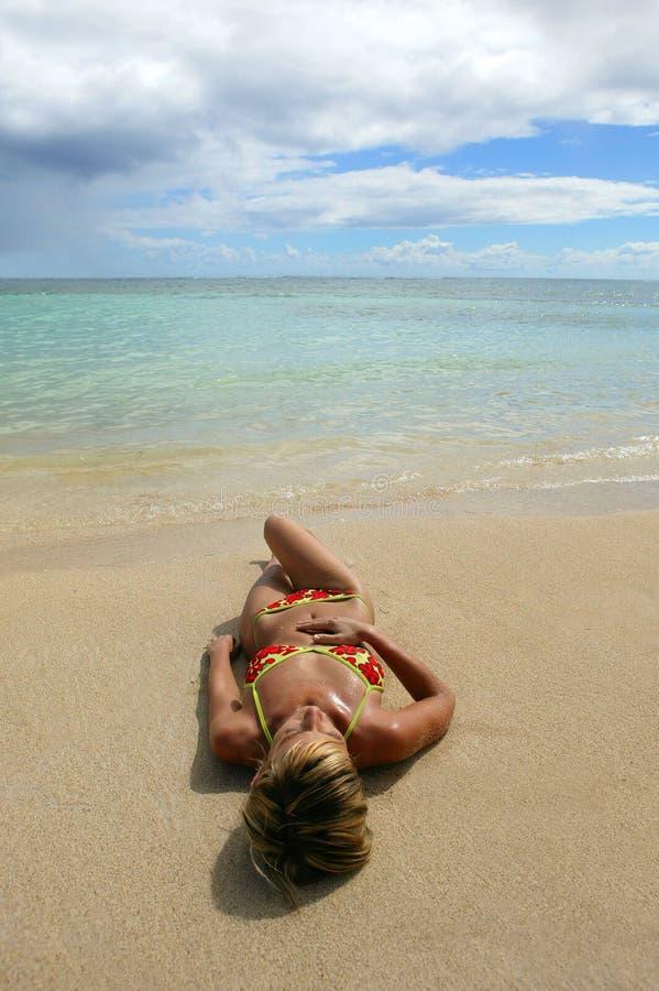 Mujer joven que miente en la playa imagen de archivo libre de regalías