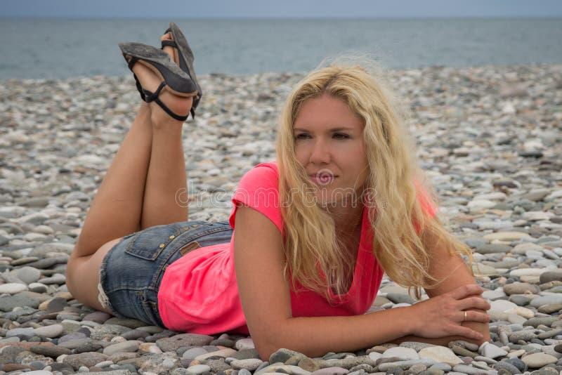 Mujer joven que miente en la playa de la guijarro-piedra imagenes de archivo