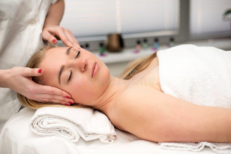 Mujer joven que miente en la tabla del masaje que recibe masaje de cara beaut fotografía de archivo