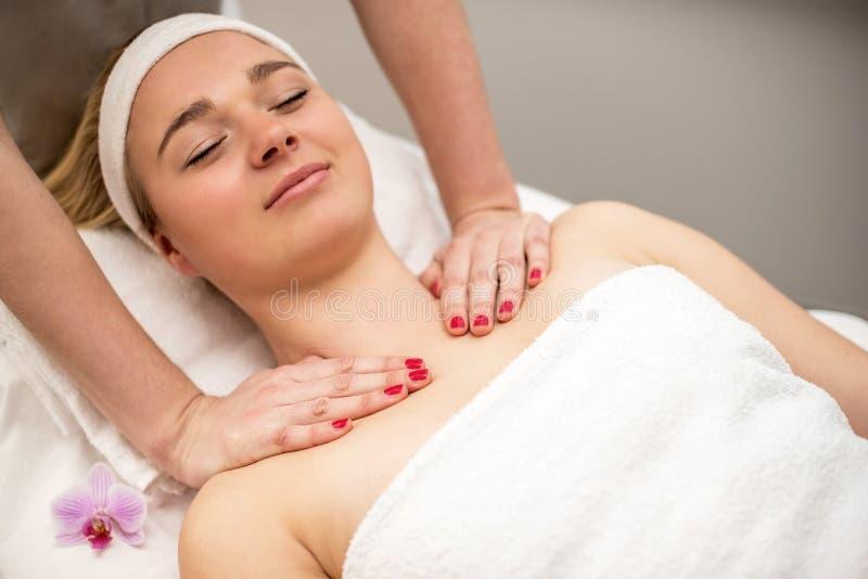 Mujer joven que miente en la tabla del masaje que recibe masaje de cara beaut imagen de archivo