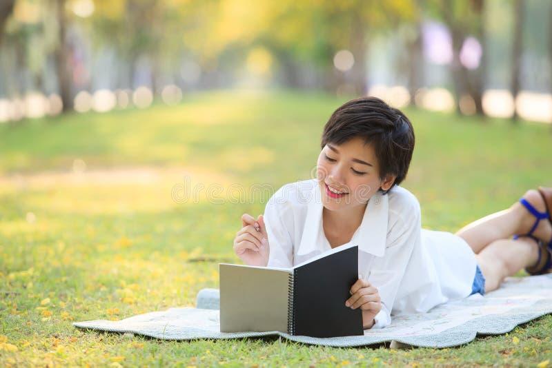 Mujer joven que miente en parque de la hierba verde con el lápiz y el cuaderno imagenes de archivo