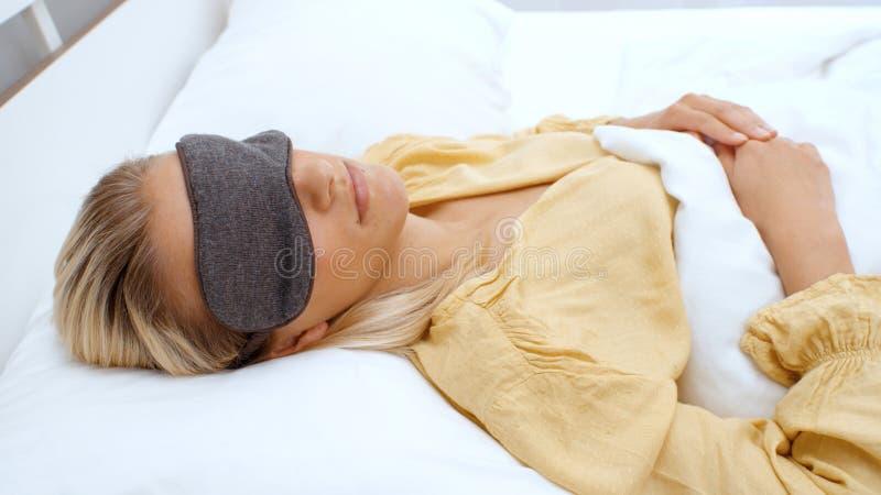 Mujer joven que miente en su cama por la mañana fotos de archivo