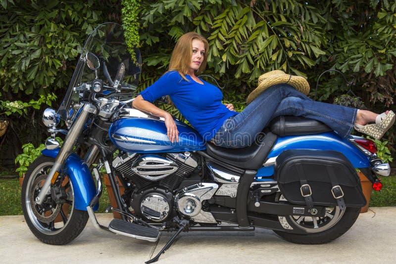 Mujer joven que miente en una motocicleta imagenes de archivo