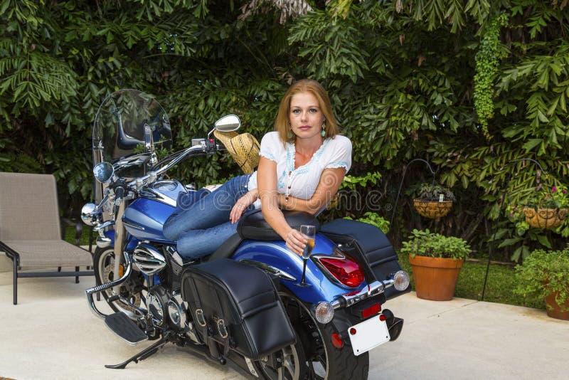 Mujer joven que miente en una motocicleta con Champán fotografía de archivo libre de regalías