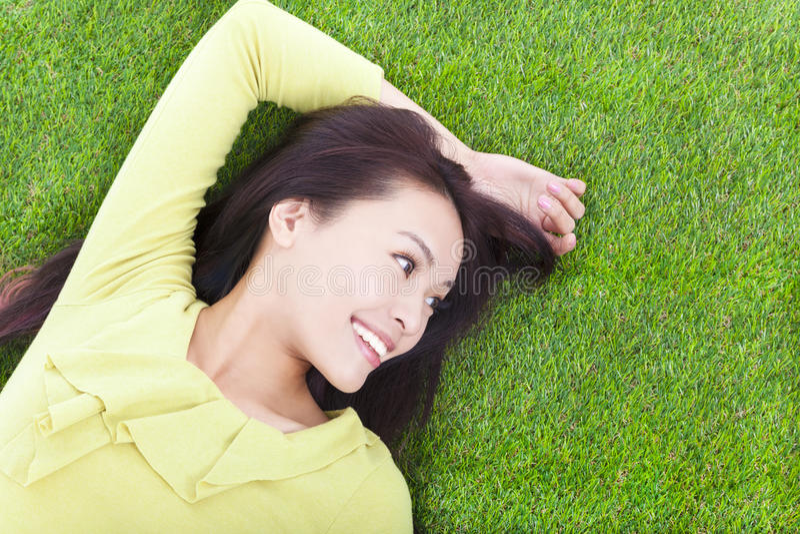 Mujer joven que miente y que parece lateral en un prado imagenes de archivo