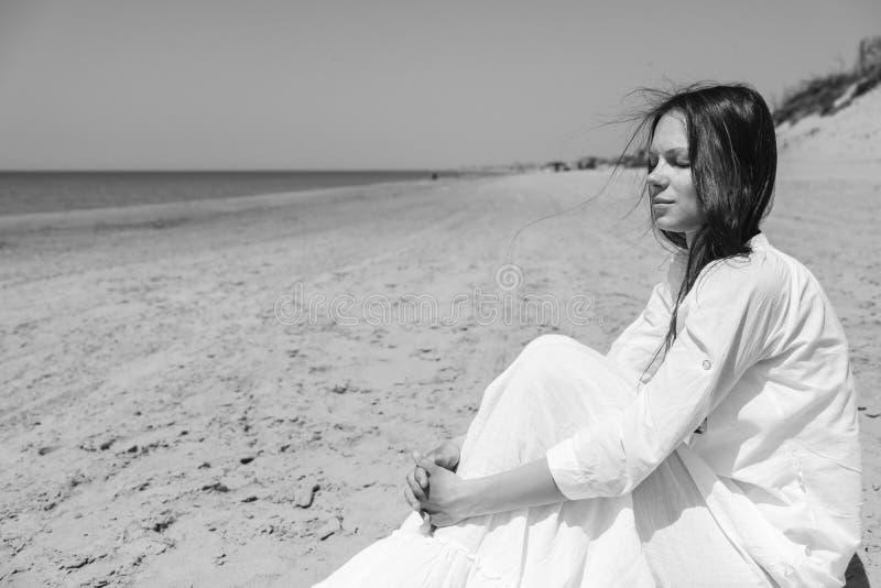 Mujer joven que mira ausente mientras que se sienta la orilla de mar imagenes de archivo