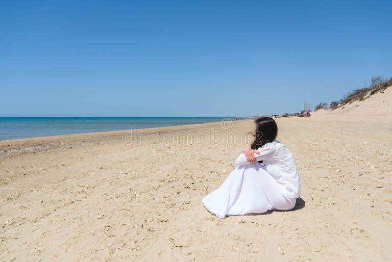 Mujer joven que mira ausente mientras que se sienta la orilla de mar fotografía de archivo libre de regalías