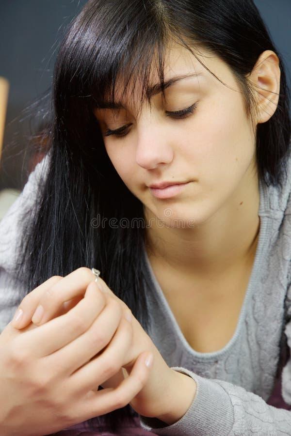 Mujer joven que mira el pensamiento del anillo de compromiso fotos de archivo libres de regalías