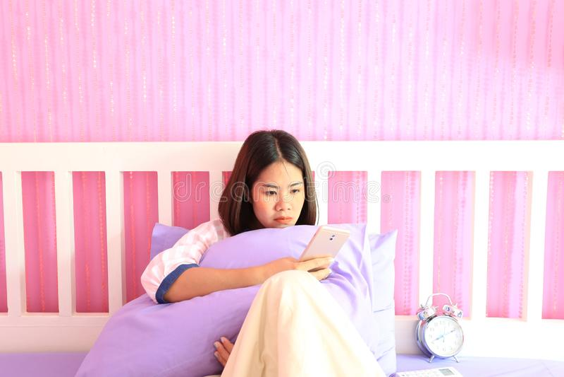 Mujer joven que mira el teléfono elegante móvil con la sensación triste y que llora en el dormitorio, emoción de la tristeza imagen de archivo