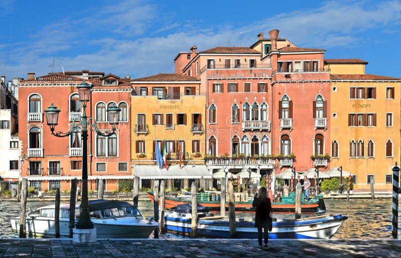 Mujer joven que mira en el canal grande con los barcos de la góndola, los edificios coloridos históricos de la fachada, las venta fotografía de archivo