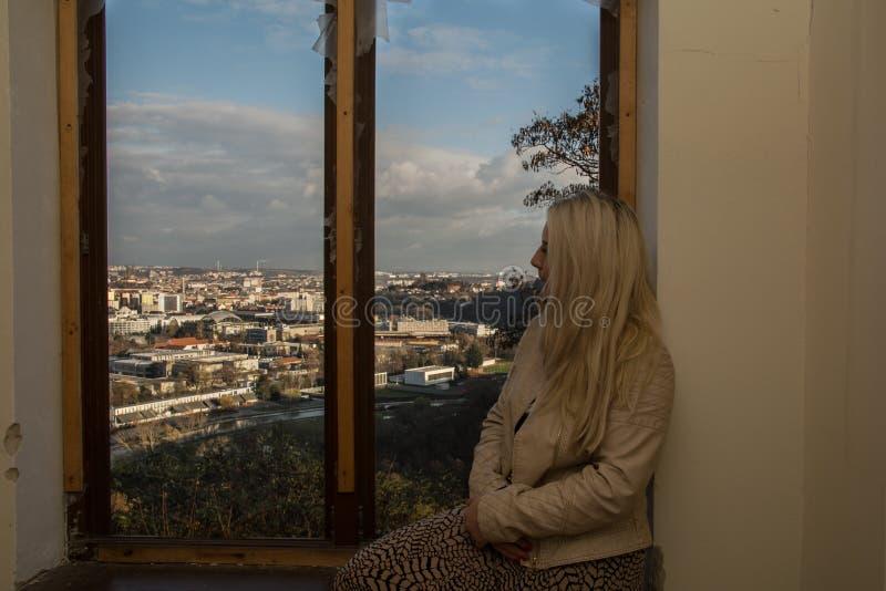 Mujer joven que mira en la ciudad de la ventana foto de archivo libre de regalías