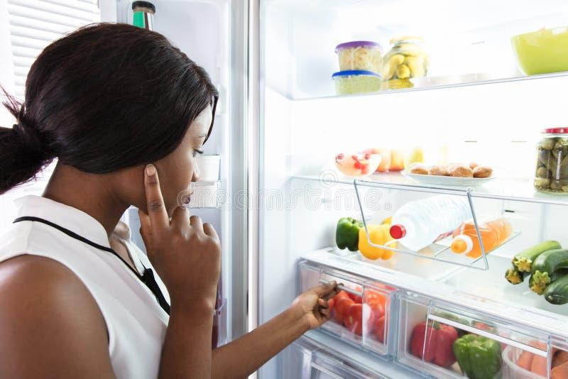 Mujer joven que mira en refrigerador imagenes de archivo