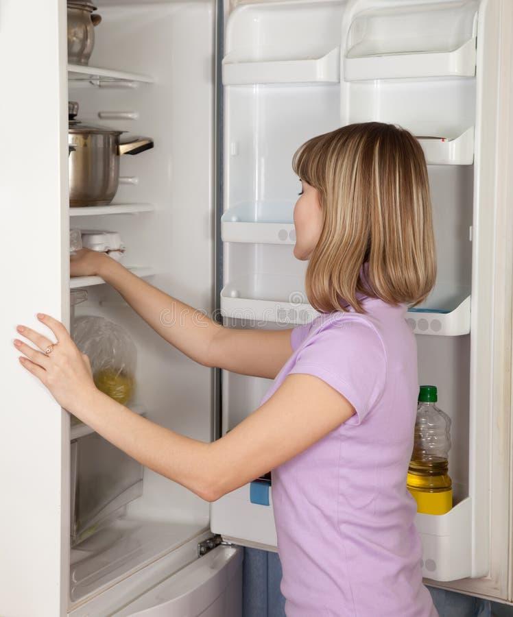 Mujer joven que mira en refrigerador fotos de archivo