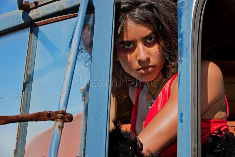 Mujer joven que mira entre el atasco de la puerta fotos de archivo