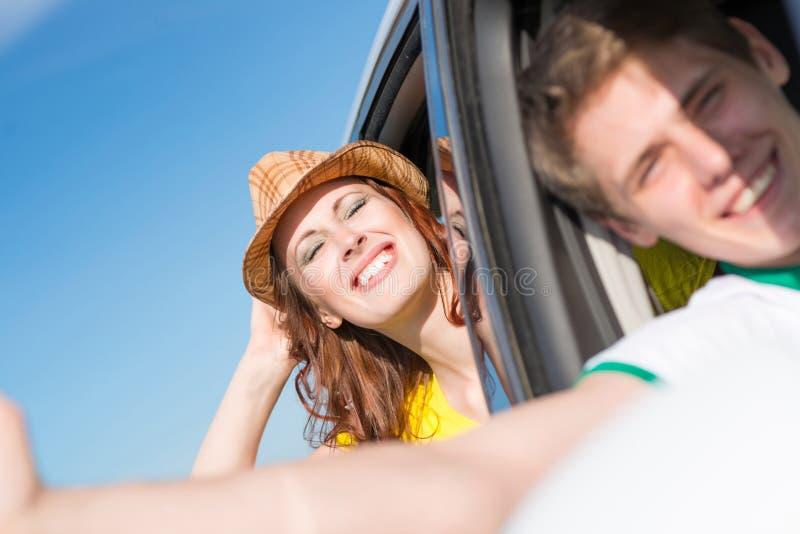 Mujer joven que mira fuera de la ventanilla del coche fotografía de archivo