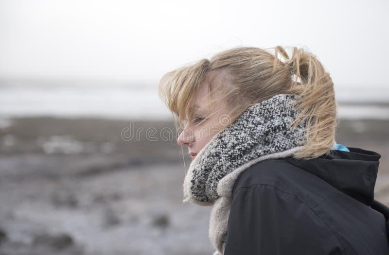 Mujer joven que mira hacia fuera sobre el mar en un día ventoso, llevado con el espacio de la copia imagen de archivo