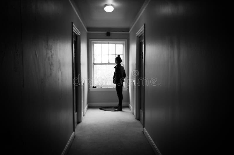 Mujer joven que mira hacia fuera una ventana en un vestíbulo oscuro fotos de archivo libres de regalías