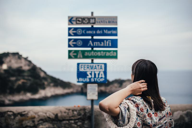 Mujer joven que mira la tabla de la muestra para la dirección Wman de vacaciones en el cosat italiano del coastSouth de las vista fotografía de archivo libre de regalías
