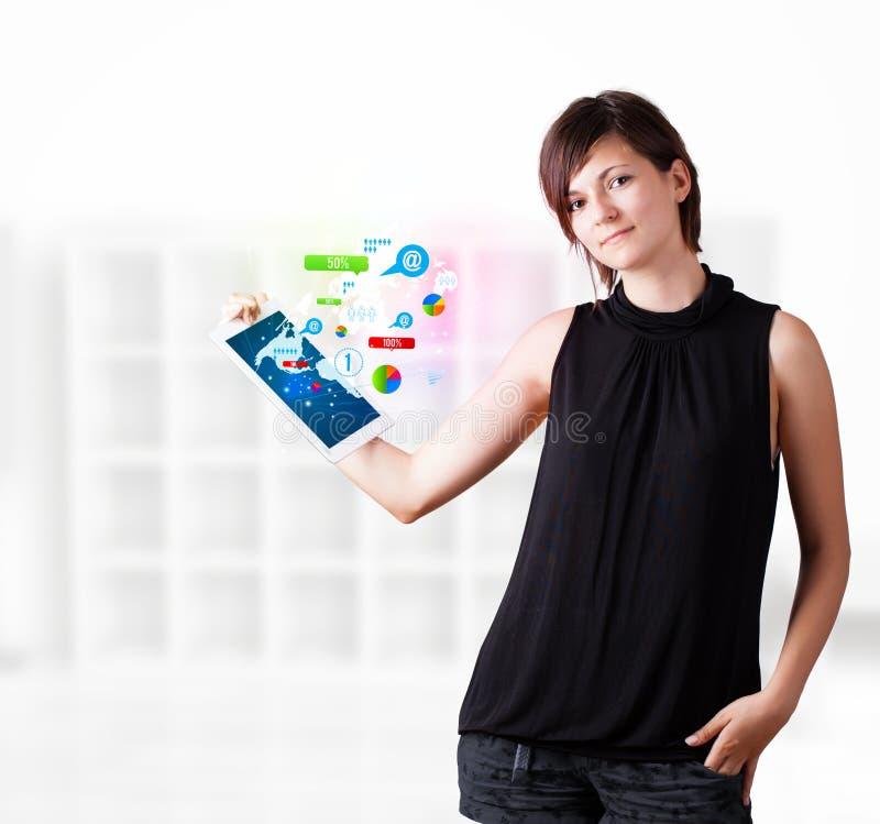 Mujer joven que mira la tableta moderna con la tecnología colorida i foto de archivo