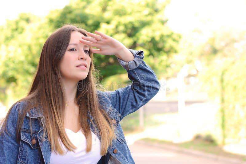 Mujer joven que mira lejos con la mano su frente fotografía de archivo