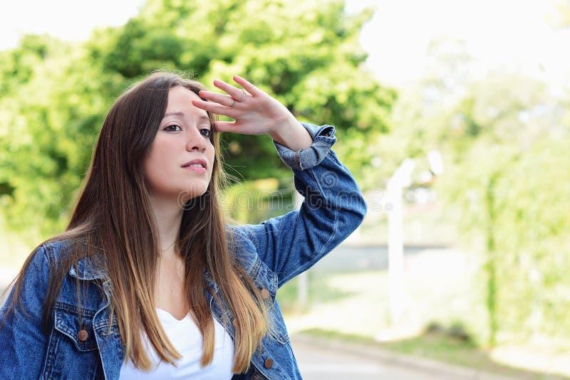 Mujer joven que mira lejos con la mano su frente foto de archivo libre de regalías