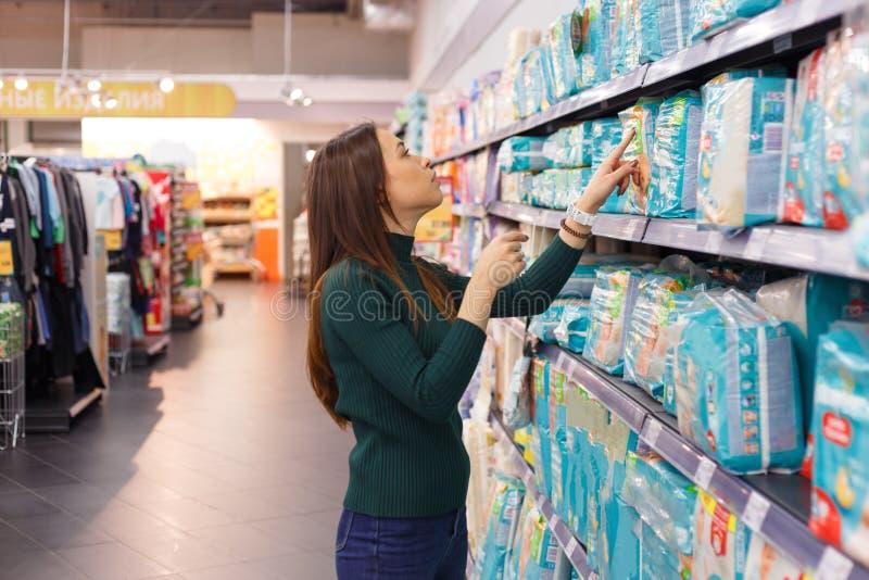Mujer joven que mira los pañales en un supermercado imagenes de archivo
