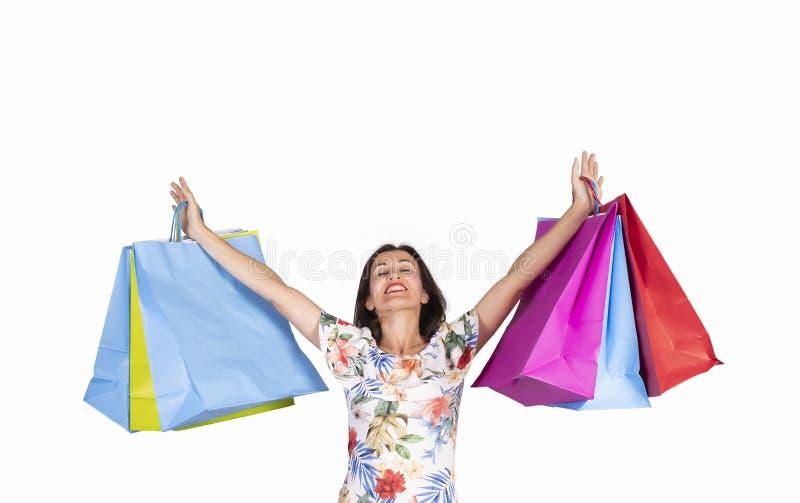 Mujer joven que mira para arriba con los bolsos de compras en el fondo blanco fotografía de archivo libre de regalías