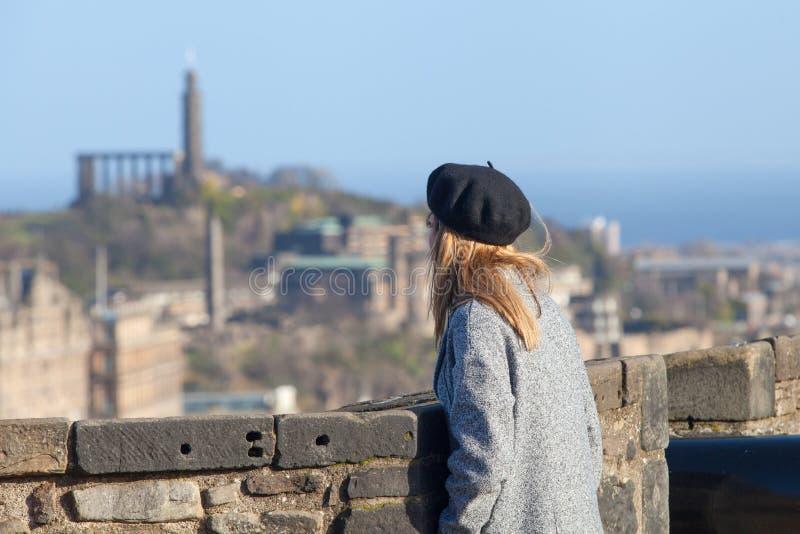 Mujer joven que mira sobre Edimburgo en el día frío fotos de archivo
