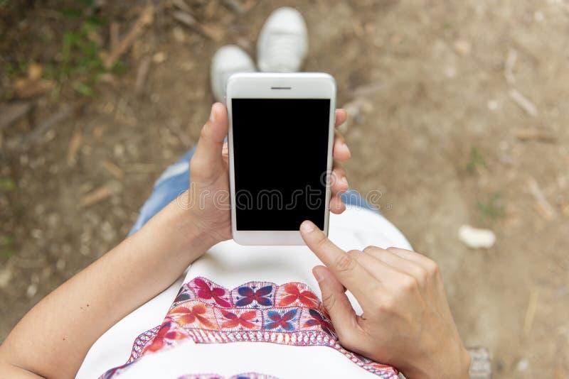 Mujer joven que mira su móvil imagen de archivo libre de regalías