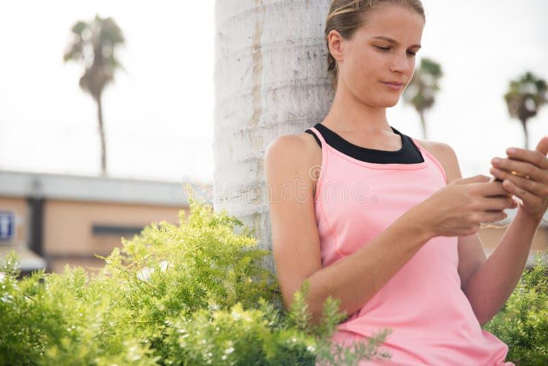Mujer joven que mira su teléfono foto de archivo libre de regalías