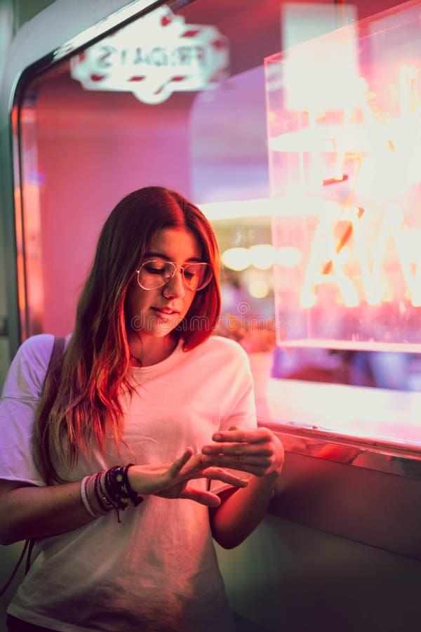 Mujer joven que mira sus clavos con los vidrios del aviador en la puerta al lado de un club con una ventana con las luces de neón foto de archivo libre de regalías