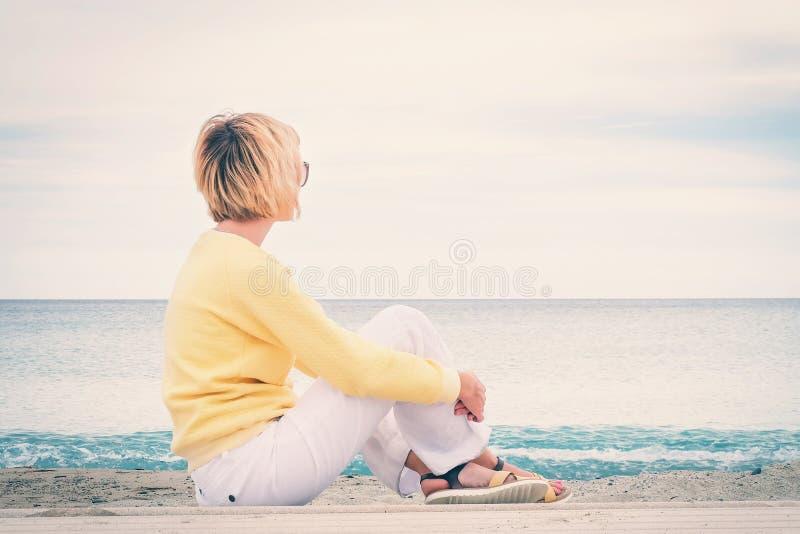 Mujer joven que mira a través del mar imagenes de archivo