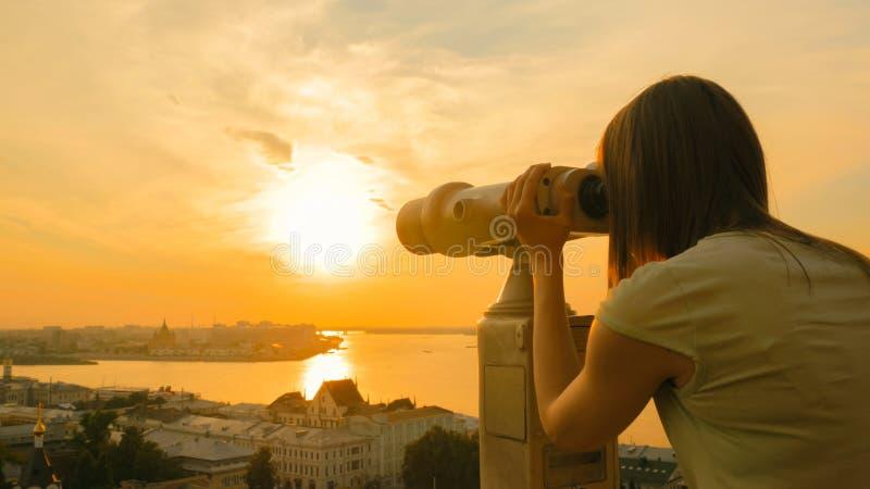 Mujer joven que mira a trav?s del telescopio tur?stico, parte hist?rica de exploraci?n de la ciudad imagen de archivo
