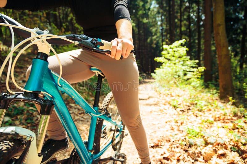 Mujer joven que monta su bici de monta?a imagen de archivo