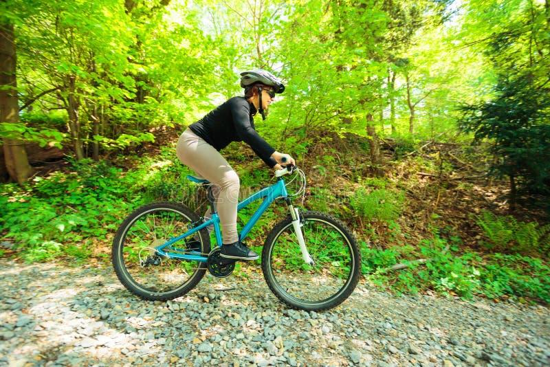 Mujer joven que monta su bici de monta?a imagen de archivo libre de regalías