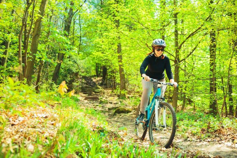 Mujer joven que monta su bici de monta?a fotografía de archivo libre de regalías