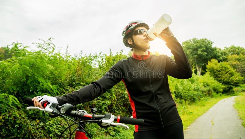 Mujer joven que monta una bici fotografía de archivo libre de regalías