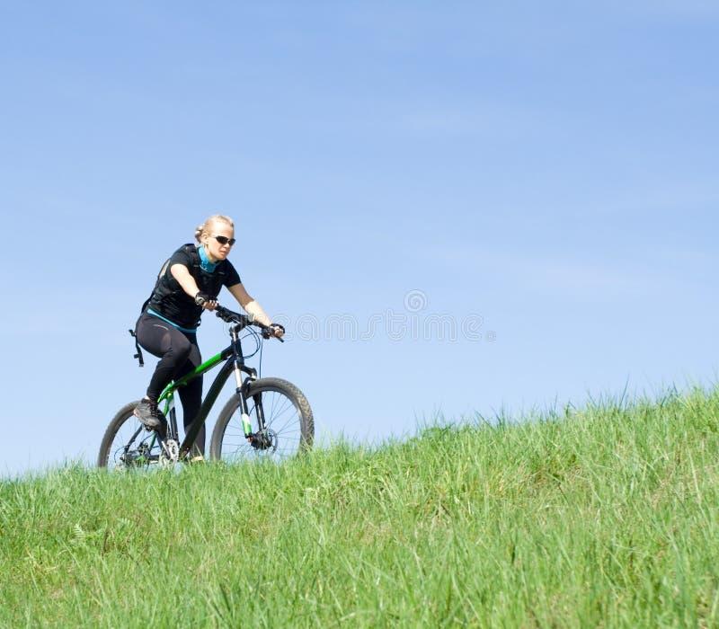 Mujer joven que monta una bici de montaña fotografía de archivo libre de regalías